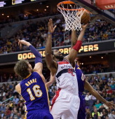 Washington Wizards power forward Nene Hilario scores over Los Angeles Lakers center Pau Gasol left and small forward Nick Young during the second...