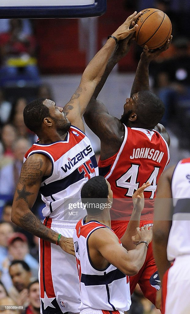 Washington Wizards power forward Trevor Booker blocks a shot by Atlanta Hawks power forward Ivan Johnson in the fourth quarter at the Verizon Center...
