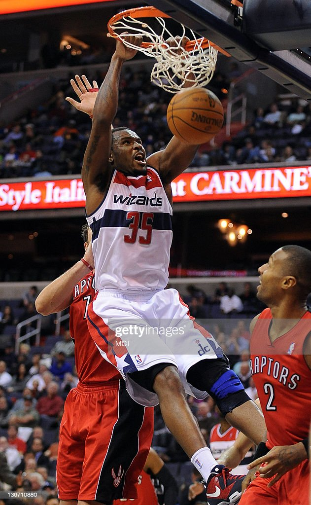 Washington Wizards power forward Trevor Booker dunks between Toronto Raptors center Andrea Bargnani and Raptors small forward James Johnson during...