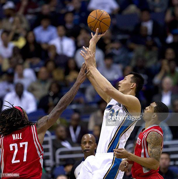 Washington Wizards power forward Yi Jianlian shoots over Houston Rockets forward Jordan Hill left and Kevin Martin during their game played at the...