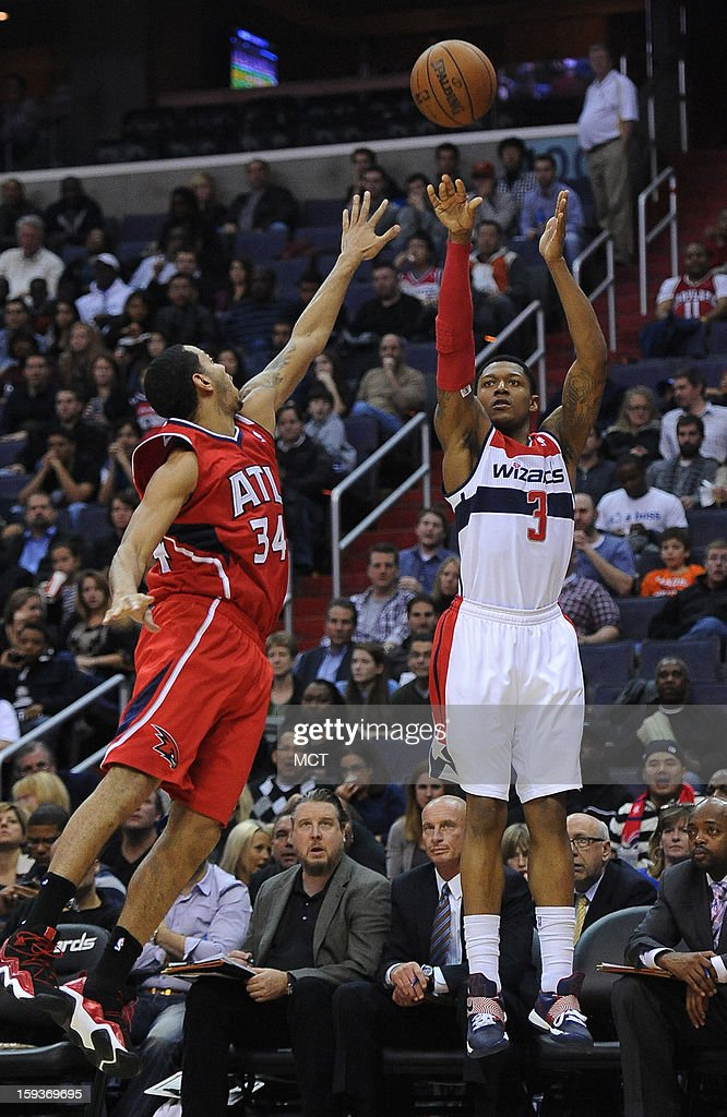 Washington Wizards shooting guard Bradley Beal (3) hits a three-point shot over Atlanta Hawks point guard Devin Harris (34) in the third quarter at the Verizon Center in Washington, D.C., Saturday, January 12, 2013. The Wizards defeated the Hawks, 93-83.