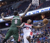Washington Wizards shooting guard Jordan Crawford looses control of the ball on his way up for a shot while being guarded by Milwaukee Bucks center...