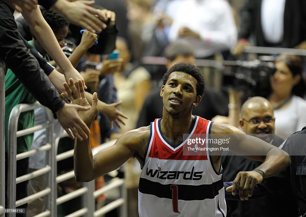 Washington Wizards shooting guard Nick Young (1) shakes hands with fans as he exits the floor after the Washington Wizards defeat the Charlotte Bobcats 92 - 75 in NBA basketball at the Verizon Center in Washington DC. January 25, 2012.