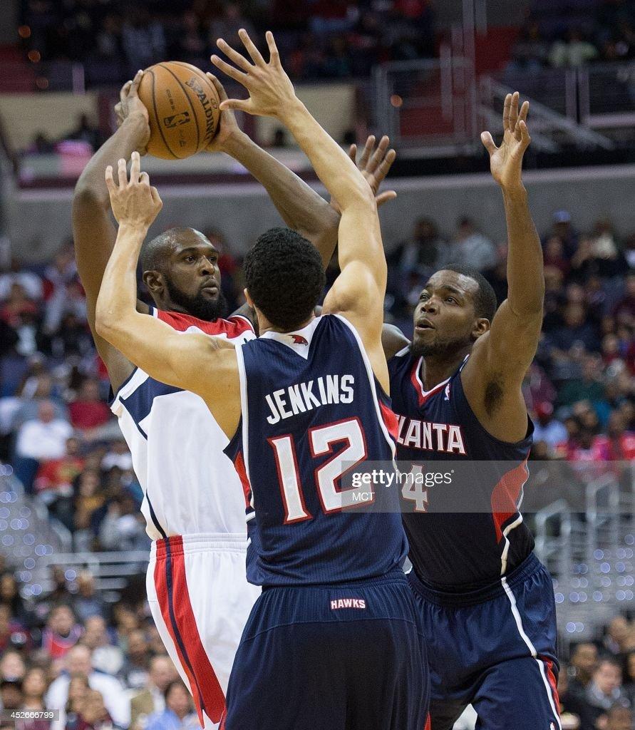 Washington Wizards small forward Chris Singleton is guarded by Atlanta Hawks shooting guard John Jenkins and power forward Paul Millsap during the...
