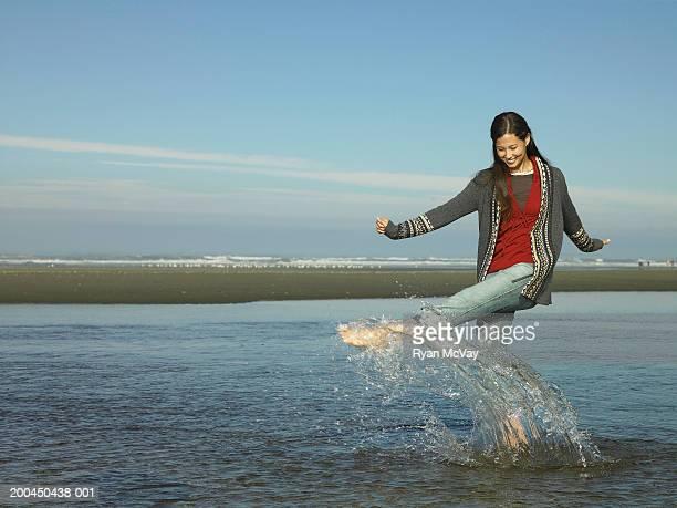 USA, Washington, young woman splashing water in tidal pool with foot