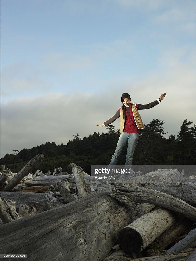 USA, Washington, young woman walking atop driftwood on beach : Stock Photo