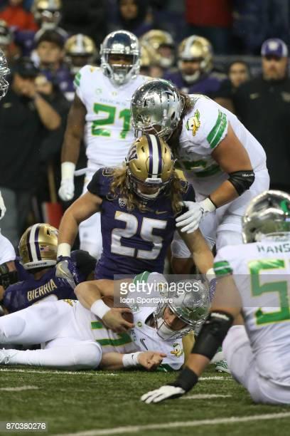 Washington's Ben BurrKirven wraps up Oregon's Braxton Burmeister at the end of a run during the college football game between the Washington Huskies...