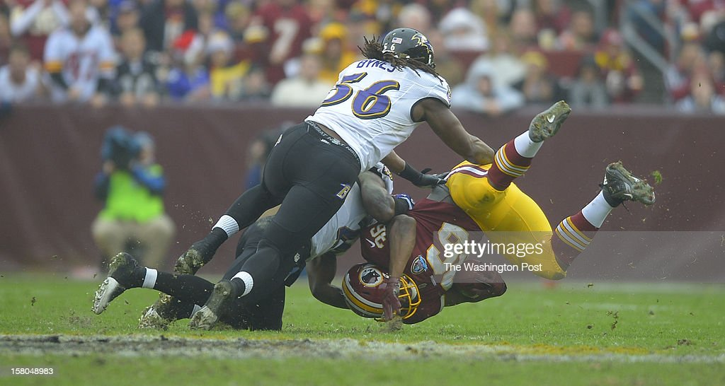 Washington's fullback Darrel Young (36) is upended by Baltimore linebacker Josh Bynes (56) and Baltimore's free safety Ed Reed (20) in the second quarter as the Washington Redskins play the Baltimore Ravens at FedEx Feild in Landover MD, December 9, 2012 .
