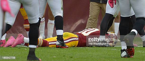 Washington's quarterback Robert Griffin III lays on the ground after getting a concussion in the 3rd quarter as the Washington Redskins play the...