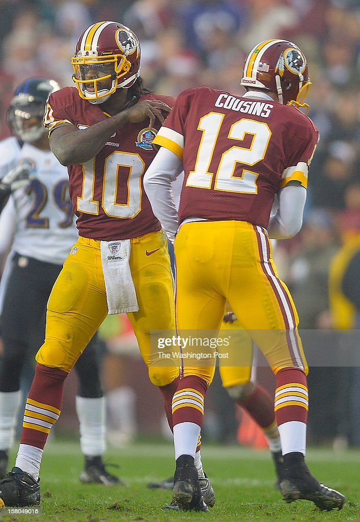 Washington's quarterback Robert Griffin III (10) left, replaces Washington's quarterback Kirk Cousins (12) for a few plays late in the 4th quarter before Cousins came back in to the win the game as the Washington Redskins defeat the Baltimore Ravens 31 - 28 at FedEx Feild in Landover MD, December 9, 2012 .