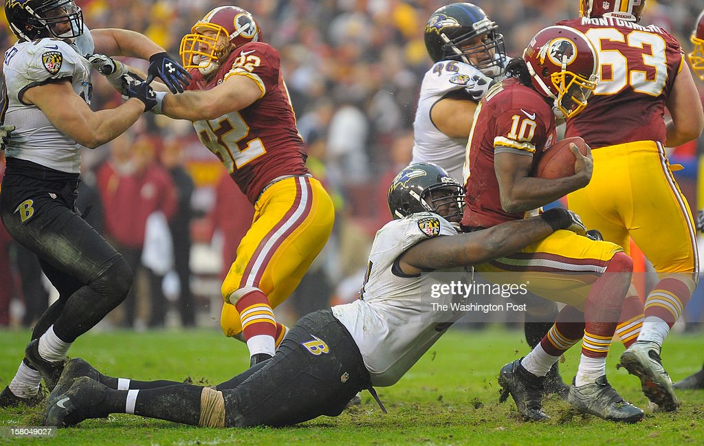 Washington's quarterback Robert Griffin III (10), right, is sacked near the Washington goal line by Baltimore's defensive end Arthur Jones (97) drilling his face mask in his back as the Washington Redskins play the Baltimore Ravens at FedEx Feild in Landover MD, December 9, 2012 .