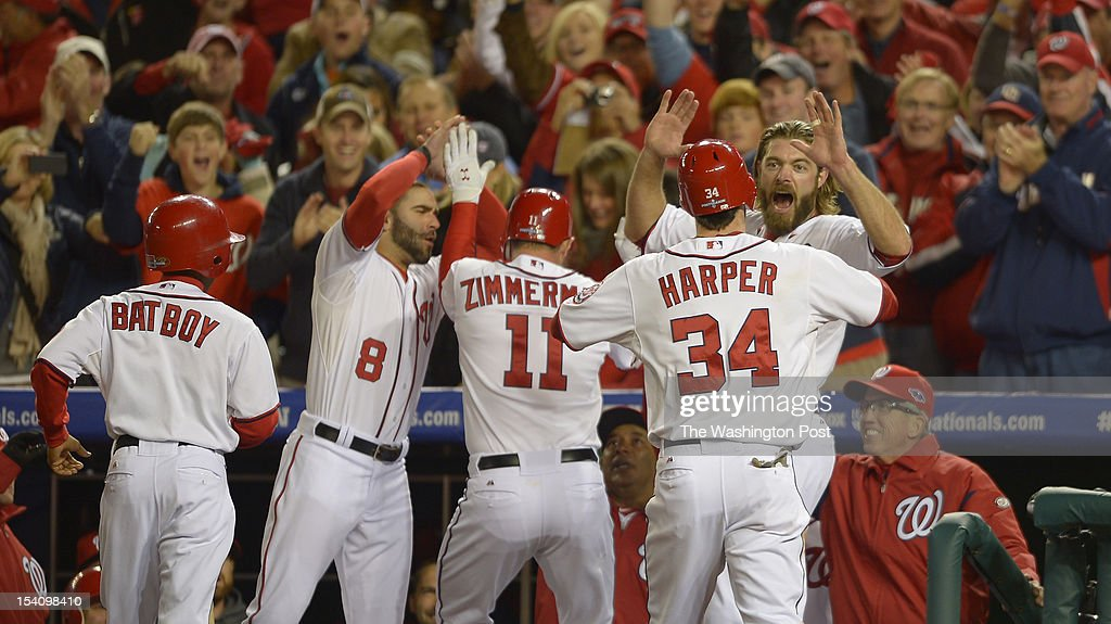 Washington's third baseman Ryan Zimmerman (11) is welcomed after a two-run homer by Washington's second baseman Danny Espinosa (8), Washington's center fielder Bryce Harper (34) and Washington's right fielder Jayson Werth (28) in the bottom of the first inning as the Washington Nationals play the St. Louis Cardinals in game 5 of the National League Divisional Playoff at Nationals Park in Washington DC, October 12, 2012