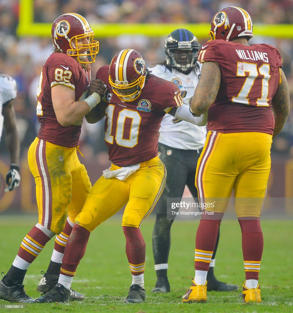 Washington's tight end Logan Paulsen (82), left, helps up an injured Washington's quarterback Robert Griffin III (10), center, along with teammate Trent Williams late in the 4th quarter as the Washington Redskins defeat the Baltimore Ravens 31 - 28 at FedEx Feild in Landover MD, December 9, 2012 .