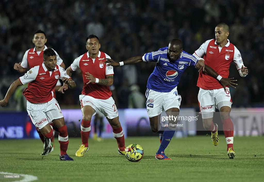 Wason Renteria of Millonarios fights for the ball with Juan Roa, Humberto Mendoza and Yulian Anchico of Independiente Santa Fe during a match between Millonarios and Independiente Santa Fe as part of the Superliga Postobon 2013 at the Nemesio Camacho Stadium on January 24, 2013 in Bogota, Colombia.