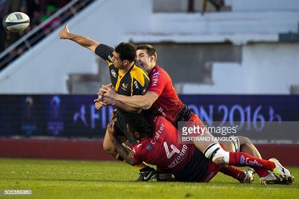 Wasps' Australian flanker George Smith makes a pass despite RC Toulon's French lock Jocelino Suta and RC Toulon's French lock Thibault Lassalle...