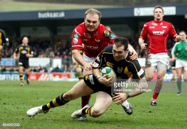 Wasps' David Doherty beats the tackle of Llanelli's Ceiron Thomas to score their third try during the Heineken Cup match at Adams Park High Wycombe