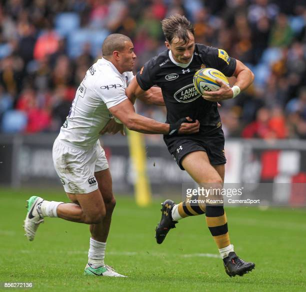 Wasps' Josh Bassett gets away from Bath Rugby's Jonathan Joseph during the Aviva Premiership match between Wasps and Bath Rugby at The Ricoh Arena on...