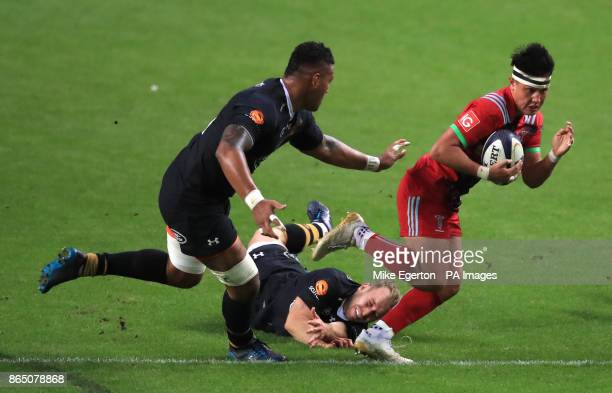 Wasps' Nathan Hughes and Dan Robson tackle Harlequins' Marcus Smith during the Champions Cup pool one match at the Ricoh Arena Coventry