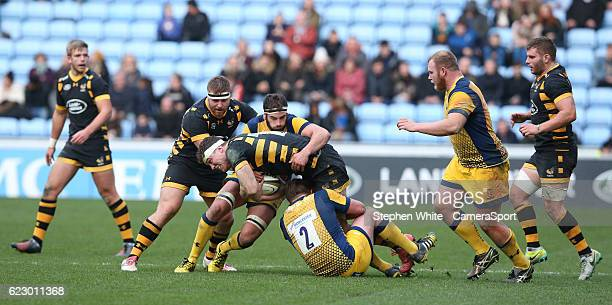 Wasps' Will Rowlands is tackled by Worcester Warriors' Jack Singleton and Sam Betty during the AngloWelsh Cup Round 1 match between Wasps and...