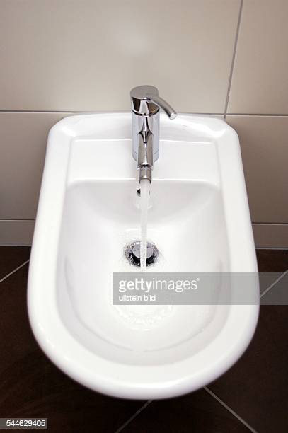 Wasser fliesst aus einem Wasserhahn ins Bidet