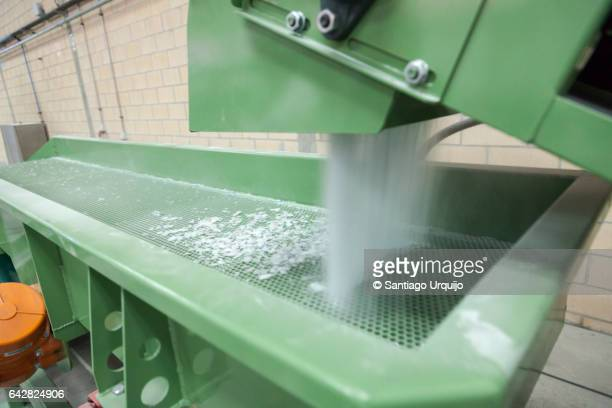 Waste fiberglass being recycled into plastic pellets