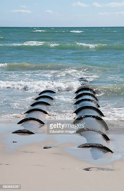 Waste outflow pipes stretch out into the sea at the Strand a seaside resort Western cape South Africa