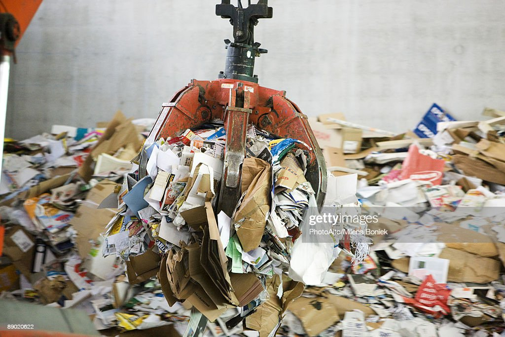 Waste paper being processed in recycling center : Stock Photo