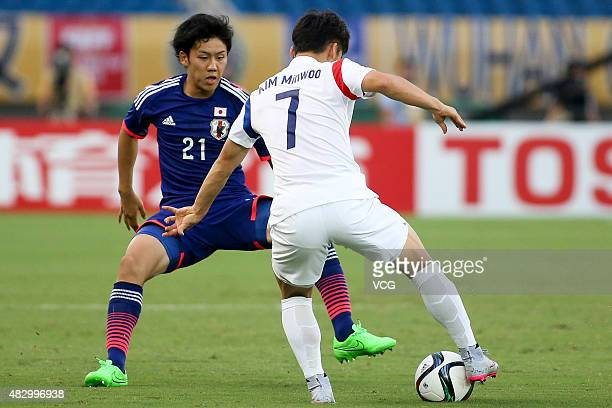 Wataru Endo of Japan and Kim Minwoo of South Korea compete for the ball in group match between Japan and South Korea during EAFF East Asian Cup 2015...