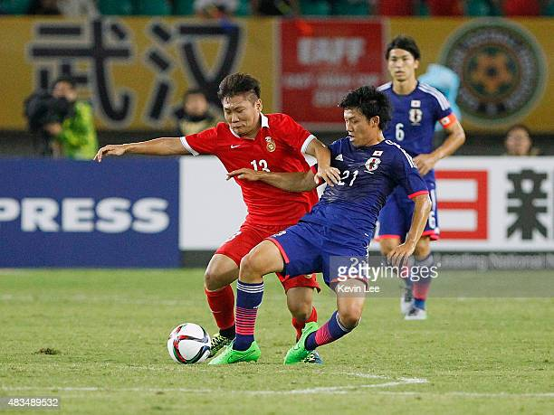 Wataru Endo of Japan battles for the ball against Liu Jianye#13 of China during the EAFF East Asian Cup 2015 final round at the Wuhan Sports Center...
