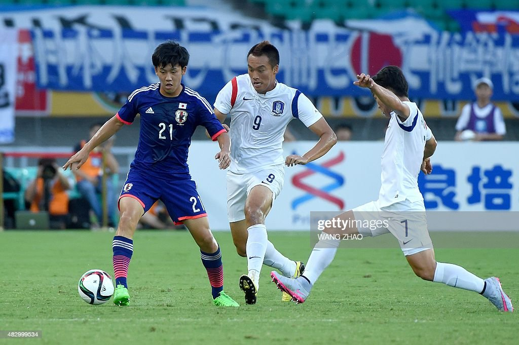 <a gi-track='captionPersonalityLinkClicked' href=/galleries/search?phrase=Wataru+Endo&family=editorial&specificpeople=7800427 ng-click='$event.stopPropagation()'>Wataru Endo</a> (L) of Japan fights for the ball with Kim Shinwook (C) of South Korea during the men's East Asian Cup football match at the Wuhan Sports Center Stadium in Wuhan on August 5, 2015.