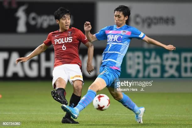 Wataru Endo of Urawa Red Diamonds and Daichi Kamada of Sagan Tosu compete for the ball during the JLeague J1 match between Sagan Tosu and Urawa Red...