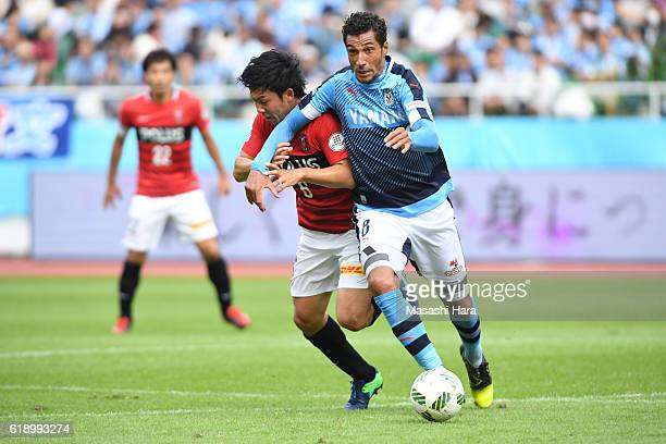 Wataru Endo of Urawa Red Diamonds and Jay Bothroyd of Jubilo Iwata compete for the ball during the JLeague match between Jubilo Iwata and Urawa Red...