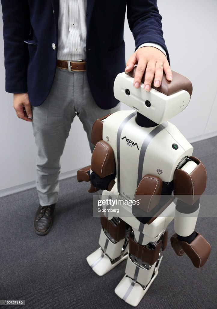 Wataru Yoshizaki, chief robot officer of Asratec Corp., poses with the company's humanoid robot 'Asra C1' in Tokyo, Japan, on Tuesday, June 17, 2014. The unit of SoftBank Corp. has unveiled an operating system that would control robots in the same way Google Inc.'s software runs smartphones and tablets. The platform called V-Sido OS can be customized for different types of robots used in home health care, construction and entertainment, Yoshizaki, said in an interview. Photographer: Tomohiro Ohsumi/Bloomberg via Getty Images