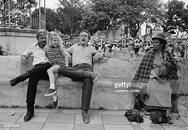 Watched by a local resident and fellow actor Robert Redford American actor Paul Newman reacts in mock pain as his daughter pushes down on his knee...