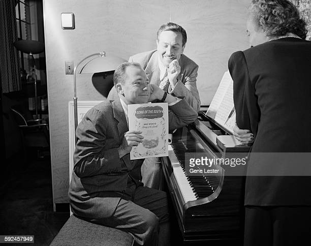 Watched by American movie producer artist and animator Walt Disney musician Johnny Mercer sits at a piano and holds up the sheet music from Disney's...