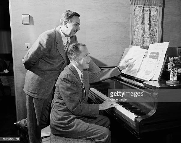 Watched by American movie producer artist and animator Walt Disney musician Johnny Mercer plays piano from the sheet music of Disney's 'Soug of the...