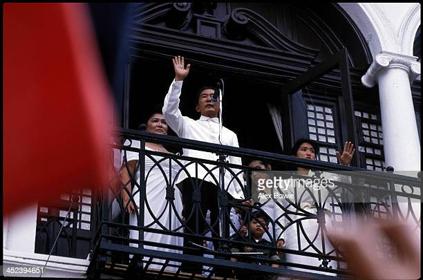 Watched by First Lady Imelda Marcos Philippine President Ferdinand Marcos waves to supporters from a balcony of the Malacanang Palace in Manila after...