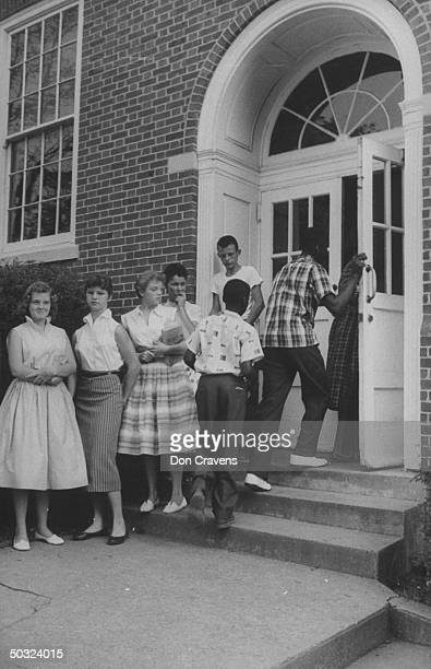 Watched by several white students African American students Maurice Soles William Latham walk through the door at recently desegregated Clinton High...
