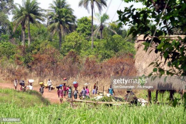 Watched over by a Pathfinder soldier local villagers flood into Lungi Loy the most northerly outpost of the British Army in Sierra Leone where troops...