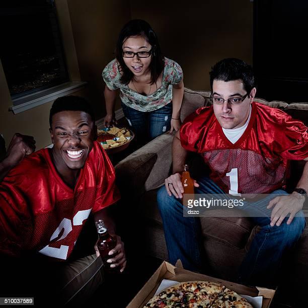 Regarder le football à la télévision-américaine jeune adulte amis