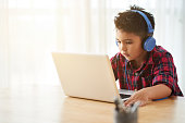Cute little boy in headphones watching something on laptop at home