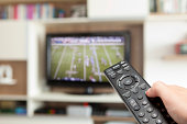 watching football with TV remote control in hand