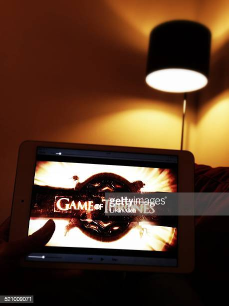 Watching Game of Thrones on mini iPad in a dark and cozy living room