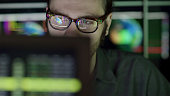 A bearded young man studying a computer screen displaying images of the earth with moving graphics. He's surrounded by out of focus, colourful displays and reflections showing moving global graphics t