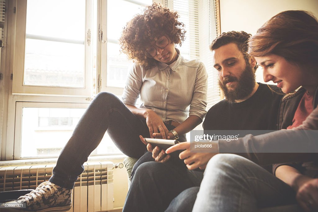 Watching pictures on the smartphone together : Stock Photo