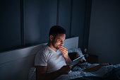 Man watching series online in bed.