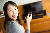 Woman with remote control switching channels