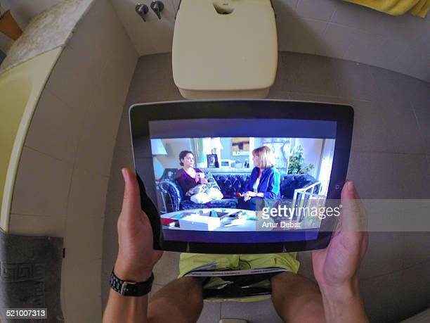 Watching television series online with iPad tablet sitting in the toilet with first person view