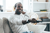 Handsome young African man watching TV and smiling while sitting on the sofa at home