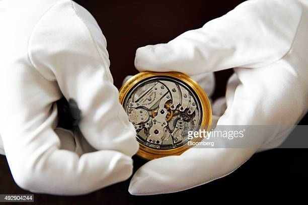 A watchmaker displays the workings of a Patek Philippe SA antique 1917 pocket watch at the Patek Philippe SA headquarters and manufacturing facility...